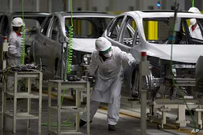 FILE - Employees work in the new multibillion-dollar Honda car plant in Celaya, in the central Mexican state of Guanajuato, Feb. 21, 2014. Many in the U.S. government, and even some in Mexico, say the new trade agreement reached in August 2018 betwee...