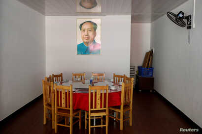 A portait of former Chinese leader Mao Zedong hangs above a dining table in a restaurant next to the Red Culture Training Center in the mountains outside Jinggangshan, Jiangxi province, China, Sept. 14, 2017.