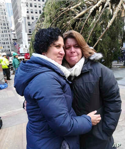 Lissette Gutierrez, left, hugs her wife, Shirley Figueroa, with the 72-foot-tall Norway spruce that the couple donated in the background, Nov. 10, 2018 in New York.