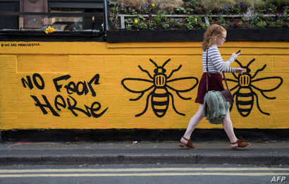 A woman passes a street-art graffiti mural, created following the May 22 terror attack at the Manchester Arena, featuring bees, which are synonymous with Manchester as a symbol of the city's industrial heritage, in Stevenson Square, Manchester.