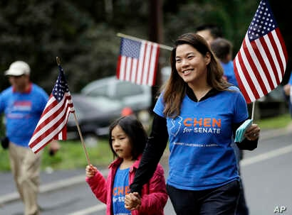 FILE - Christine Lui Chen, right, who is running for state senate during the November elections, walks with her daughter Lily Chen, 6, while participating in the Bridgewater Memorial Day Parade in Bridgewater, N.J., May 29, 2017.
