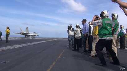 US Secretary of Defense Ash Carter (center, in blue shirt) watches a jet take off from the USS John C. Stennis in the South China Sea (C.Babb/VOA)