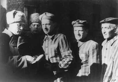 FILE- In this file photo dated January 1945, three Auschwitz prisoners, right, talk with Soviet soldiers after the Nazi concentration camp Auschwitz, in Poland, was liberated by the Russians.