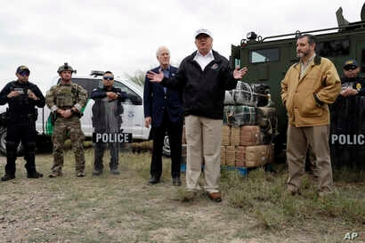 President Donald Trump speaks as tours the U.S. border with Mexico at the Rio Grande on the southern border, Thursday, Jan. 10, 2019, in McAllen, Texas, as Sen. John Cornyn, R-Texas, left, and Sen. Ted Cruz, R-Texas, listen.