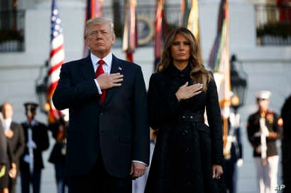 President Donald Trump and first lady Melania Trump stand for a moment of silence to mark the anniversary of the Sept. 11 terrorist attacks, on the South Lawn of the White House, Sept. 11, 2017, in Washington.