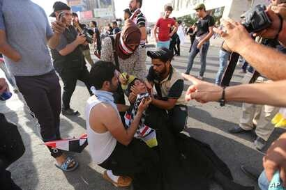 A female protester is assisted after reacting to tear gas fired by security forces in central Baghdad, Iraq, May 27, 2016.