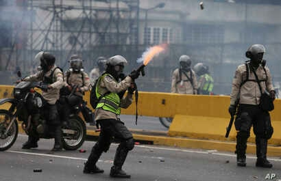 A police officer fires tear gas against anti-government protesters in Caracas, Venezuela, April 20, 2017.