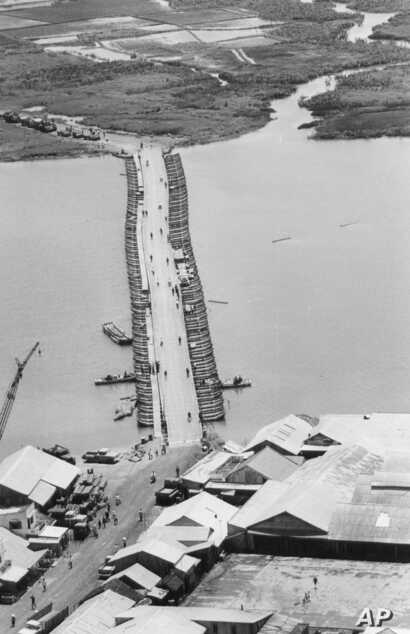 FILE - Military traffic is halted as U.S. Army engineers finish repairing a pontoon bridge damaged by a Viet Cong underwater mine, August 1968. Linking Saigon with the Mekong Delta, the bridge over the Oriental River replaced the permanent bridge, bl...