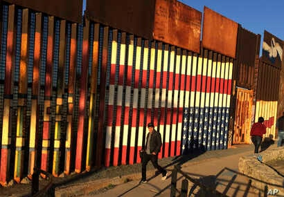 People pass graffiti along the border structure in Tijuana, Mexico, Jan. 25, 2017.