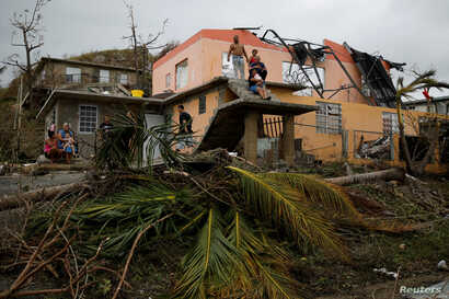 People rest outside a damaged house after the area was hit by Hurricane Maria in Yabucoa, Puerto Rico, Sept. 22, 2017.