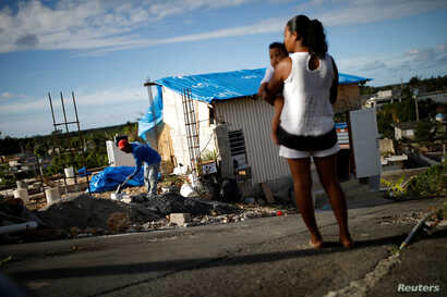 Samuel Vasquez rebuilds his house, which was partially destroyed by Hurricane Maria, while his wife Ysamar Figueroa looks on, whilst carrying their son Saniel, Dec 11, 2017.