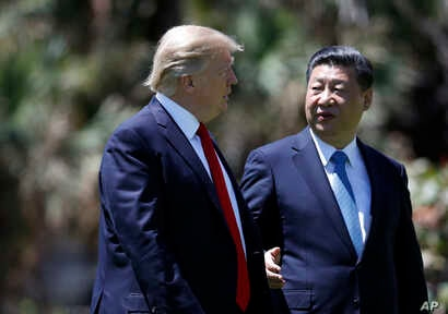 President Donald Trump and Chinese President Xi Jinping walk together after their meetings at Mar-a-Lago, April 7, 2017, in Palm Beach, Florida.