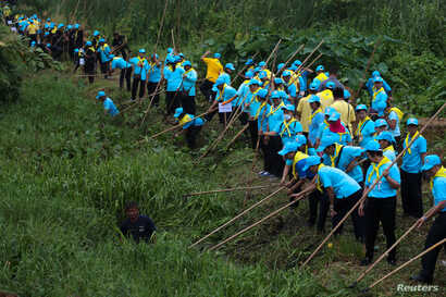King's volunteers wearing blue caps and yellow foulards clean a canal in Bangkok, Aug. 8, 2018.
