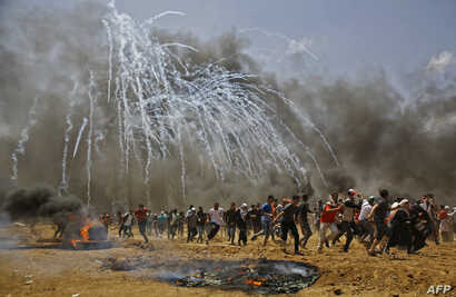 Palestinians run for cover from tear gas during clashes with Israeli security forces near the border between Israel and the Gaza Strip, east of Jabalia, May 14, 2018, as Palestinians protest over the inauguration of the U.S. embassy following its con...