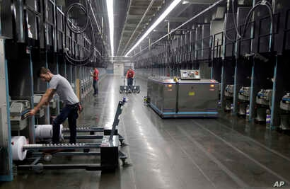 Workers exchange spools of thread as a robot picks up thread made from recycled plastic bottles at the Repreve Bottle Processing Center, part of the Unifi textile company in Yadkinville, N.C., Oct. 21, 2016.  America has lost more than 7 million fact...