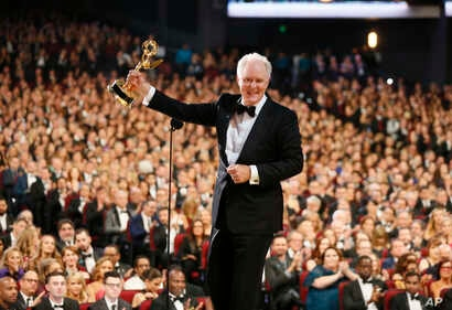 """John Lithgow accepts the award for outstanding supporting actor in a drama series """"The Crown"""" on the red carpet stage at the 69th Primetime Emmy Awards, Sept. 17, 2017, at the Microsoft Theater in Los Angeles."""
