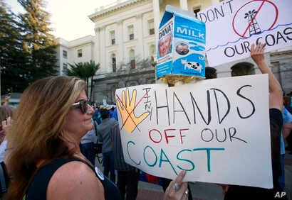 Bethany Webb, of Huntington Beach, joins other protesters at a rally against oil drilling off the California coast at the state Capitol before marching to a hearing by the U.S. Bureau of Ocean Energy Management, Feb. 8, 2018, in Sacramento, Calif.