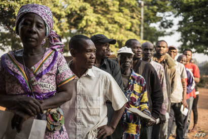 Voters queue outside a polling station in Bangui on Dec. 13, 2015 to vote for the constitutional referendum, seen as a test run for presidential and parliamentary polls scheduled two weeks later aimed at ending two years of sectarian strife in the Ce...