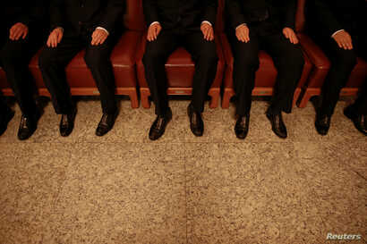 FILE - Security agents wear black as they sit on chairs inside the Great Hall of the People, where sessions of the National People's Congress and the Chinese People's Political Consultative Conference take place, in Beijing, China, March 5, 2016.