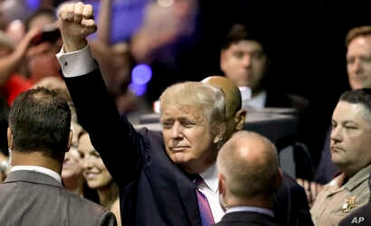 Republican presidential candidate Donald Trump raises his arm as he leaves after a rally in The Woodlands, Texas, June 17, 2016.