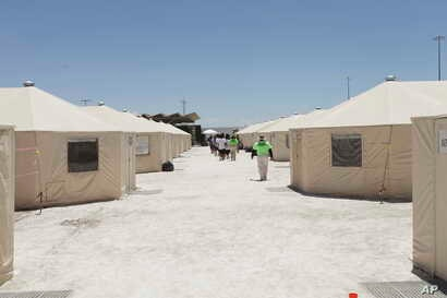 The undated photo released by U.S. Department of Health and Human Services shows detainees walk in a line at the HHS' unaccompanied alien children program facility at Tornillo, Texas.