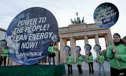 Greenpeace activists protest in front of the Brandenburg Gate in Berlin, Germany, April 13, 2014.