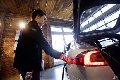FILE - Tesla product specialist Kat Brand demonstrates how to plug in the electric car at a dealership for the vehicle, in Seattle, Feb. 4, 2015.