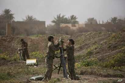 U.S.-backed Syrian Democratic Forces (SDF) soldiers prepare to fire mortars at Islamic State militant positions in Baghuz, Syria, March 13, 2019.