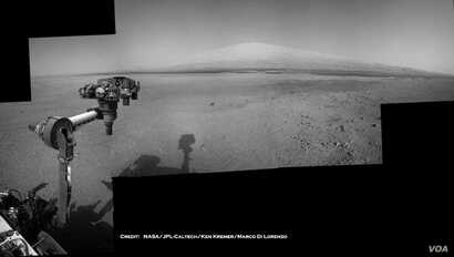 The Mars Curiosity rover's robotic arm takes aim at Mount Sharp in a mosaic that combines navigation-camera imagery from Sols 2, 12 and 14 (Aug. 8, 18 and 20). The shadow of the rover's camera mast is visible in the center foreground.