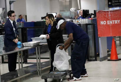 An employee of the Chef Creole restaurant, right, unloads meals for TSA workers at Miami International Airport,  Jan. 15, 2019, in Miami.