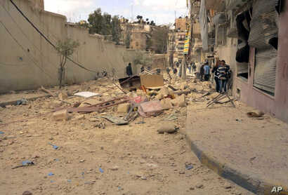 FILE - People walk amid the wreckage of damaged buildings in a street hit by shelling in Aleppo, Syria, Apr. 11, 2015.