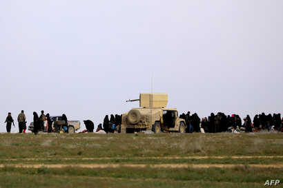 Fighters of the Syrian Democratic Forces (SDF) accompany women and children as they wait in a field after fleeing the Islamic State (IS) group's last holdout of Baghuz in Syria, Feb. 21, 2019.