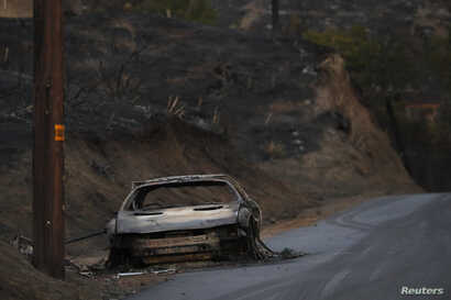 The burnt wreckage of a vehicle is seen along a road in the aftermath of the Woolsey fire in Malibu, Southern California, Nov.11, 2018.