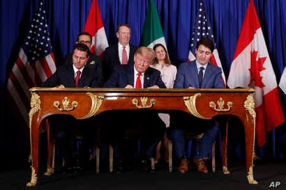 President Donald Trump, Canada's Prime Minister Justin Trudeau, right, and Mexico's then-President Enrique Pena Nieto, left, participate in the USMCA signing ceremony, Nov. 30, 2018, in Buenos Aires, Argentina.