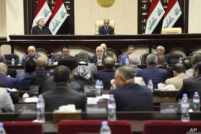 Iraqi Prime Minister Haider al-Abadi, center, attends a session of the Iraqi Parliament, in Baghdad, Iraq, Wednesday, Sept. 27, 2017. Al-Abadi on Wednesday ordered the Kurdish region to hand over control of its airports to federal authorities or face...