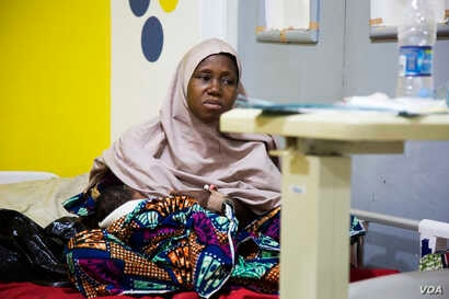 Aisha Suleiman, 32, breastfeeds her day-old child. She experienced postpartum hemorrhage during the delivery and lost three pints of blood.(Photo: Chika Oduah for VOA)