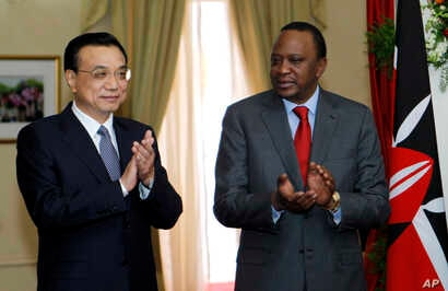 Chinese Premier Li Keqiang, left, and Kenya's President Uhuru Kenyatta applaud after the signing of the Standard Gauge Railway agreement with China at the State House in Nairobi, May 11, 2014.
