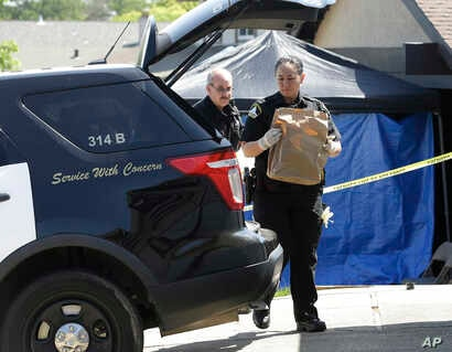 Sacramento sheriff's deputies carry evidence taken from the home of suspect Joseph DeAngelo to a sheriff's vehicle, April 26, 2018, in Citrus Heights, Calif. DeAngelo, 72, was taken into custody, Tuesday, on suspicion of committing at least 12 slayin...