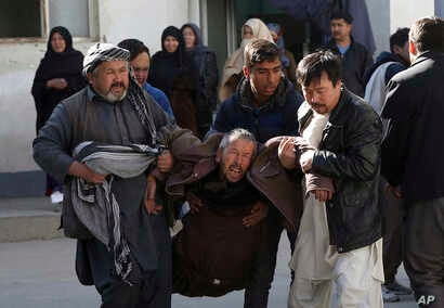A distraught man is carried away following a suicide attack in Kabul, Afghanistan, Dec. 28, 2017. Authorities say attackers stormed the Shiite Muslim cultural center in the Afghan capital Kabul, setting off multiple bombs and killing dozens.