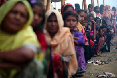Rohingya refugees line up to receive humanitarian aid in Balukhali refugee camp near Cox's Bazar, Bangladesh, Oct. 26, 2017.