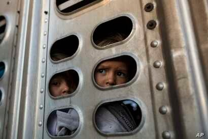 A couple of Central American migrant girls, part of the caravan hoping to reach the U.S. border, get a ride in a chicken truck, in Irapuato, Mexico, Nov. 12, 2018.
