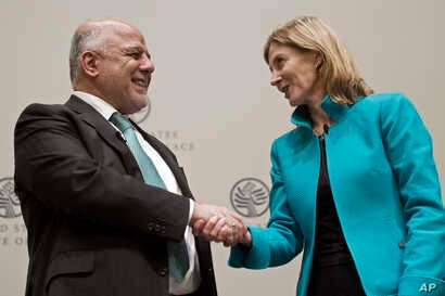 Prime Minister of Iraq Haider al-Abadi shakes hands with Nancy Lindborg, president of the United States Institute of Peace, after speaking at the institute in Washington, March 20, 2017.