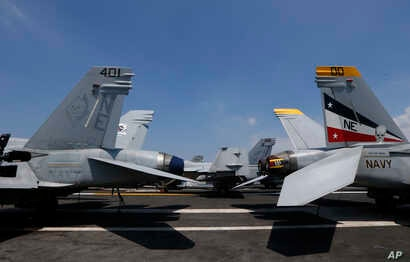 U.S. military aircraft sit on the flight deck of the USS Carl Vinson aircraft carrier anchored off Manila, Philippines, Feb. 17, 2018. Lt. Cmdr. Tim Hawkins said American forces will continue to patrol the South China Sea wherever international law a
