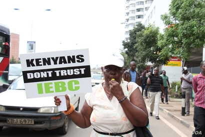 A Kenyan protester holds a sign cautioning against trusting the Independent Electoral Boundaries Commission, in Nairobi. (VOA/ M. Yusuf)