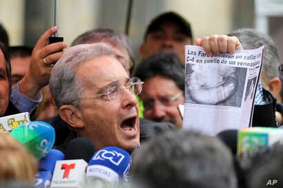 """Former President and opposition Senator Alvaro Uribe shows a clip of a news article with a headline reading in Spanish """"FARC puts a C4 collar around the neck of a Venezuelan,"""" after voting in a referendum to decide whether or not to support a peace d..."""