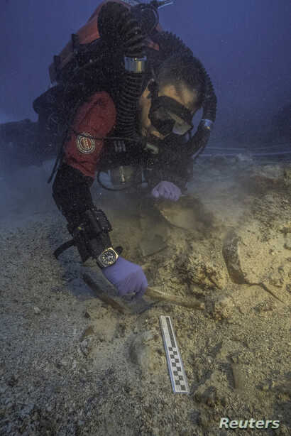 A diver works next to skeletal remains found at an ancient shipwreck near the island of Antikythera, Greece, Sept. 6, 2016.