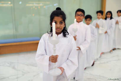 Expat children hold the candles while serving during the Mass at St. Francis of Assisi Catholic Church in Jebel Ali, in Dubai, UAE Jan. 18, 2019.
