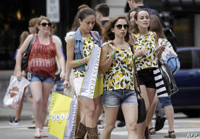 FILE - Consumers hold shopping bags as they walk along Michigan Avenue on July 29, 2016 in Chicago, Illinois.