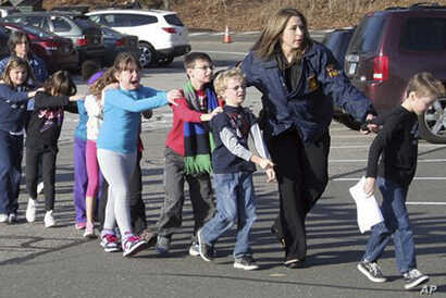 In this photo provided by the Newtown Bee, Connecticut State Police lead children from the Sandy Hook Elementary School in Newtown, Conn., following a reported shooting there, Dec. 14, 2012.