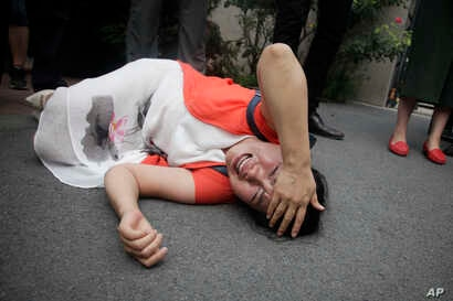 Fan Lili, the wife of imprisoned activist Gou Hongguo, lies on the ground in tears following an interaction with a plainclothed police officer outside the Tianjin No. 2 Intermediate People's Court in Tianjin, China on Aug. 1, 2016.